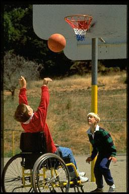 Disabled boy in a wheelchair shoots hoops with his friend at school,Orinda,CA